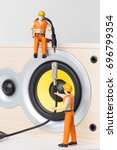 Small photo of The concept of electronic equipment repair. Miniature toy engineers fixing broken wires. Close-up view.