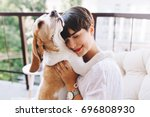 Stock photo close up portrait of pleased girl with short brown hair embracing funny beagle dog with eyes closed 696808930