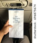 Small photo of Kuala Lumpur, Malaysia - 10 August 2017: Passenger holding air sickness bag in Malaysia Airline (MAS) flight before take off.