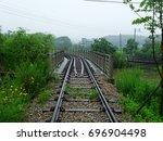A Railway Bridge With Trees An...