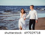 Small photo of Groom and bride run along the shore against the wind
