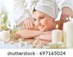 girl lying down on a massage bed | Shutterstock . vector #697165024