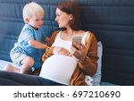 pregnant mother and son looking ... | Shutterstock . vector #697210690