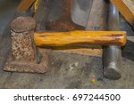 Small photo of A rusty flatter that is to be struck by a sledgehammer is found in the blacksmith shop.