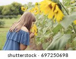 portrait girl smelling sunflower | Shutterstock . vector #697250698