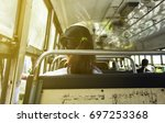 Small photo of Within the old Thailand Bangkok bus in the morning. there is light in the sun. and there are women in uniform sitting on a chair full of wrinkles. by next to the bus window to travel to work.