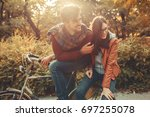 young couple riding bicycle... | Shutterstock . vector #697255078