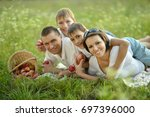 family lying on grass | Shutterstock . vector #697396000