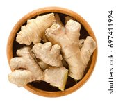 ginger roots in wooden bowl.... | Shutterstock . vector #697411924