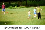 BRATISLAVA, SLOVAKIA - August 12, 2017: A family of father, mother and three kids playing football in the park - stock photo