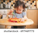 baby girl eating messy... | Shutterstock . vector #697469773