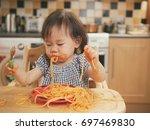 baby girl eating messy... | Shutterstock . vector #697469830