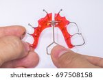 Small photo of Hands on demonstration on using a special key to activate the expansion screw of a removable orthodontic appliance to separate the two halves down the middle.