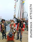 Small photo of HALIFAX, CANADA - JUL 29, 2017: Members of the Pirates of Halifax troupe pose with tourists in front of The Bluenose at the Tall Ships event.