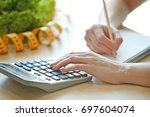 young woman calculating... | Shutterstock . vector #697604074