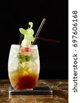 Small photo of Mai Tai punch. In a cocktail shaker with ice . combine Malibu . Amaretto and fruit juices Garnish with mint leaves and enjoy. dark background.