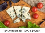 pieces of cheese with mold on... | Shutterstock . vector #697619284