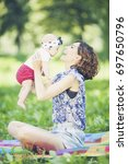young beautiful mother sits on... | Shutterstock . vector #697650796