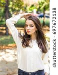 the girl is walking in the park   Shutterstock . vector #697672138