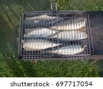 a fish. grilled on charcoal. in ... | Shutterstock . vector #697717054