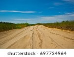 sandy dirt road with wild grass ... | Shutterstock . vector #697734964