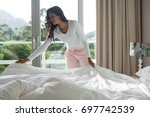 Stock photo young woman making bed at home 697742539