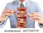 businessman building tower of... | Shutterstock . vector #697745779