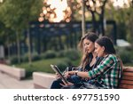 modern girls sitting on wooden... | Shutterstock . vector #697751590