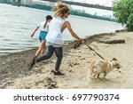 beautiful young couple with dog ... | Shutterstock . vector #697790374