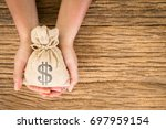 women hold a money bag on the... | Shutterstock . vector #697959154