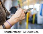 woman using smartphone in train ... | Shutterstock . vector #698006926