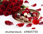 Stock photo gold plate of luxury chocolates with red roses 69805750