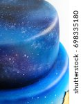 Small photo of Artistic two-tiered cake with the image of the cosmos drawn by airbrush. Galaxy, stars in the night sky and silhouettes of trees. Cutout