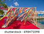Small photo of ANGRA DO HEROISMO, AZORES, PORTUGAL - JUNE 22, 2017: Numerous color strips tied to wooden frames, a seasonal decor at promenade of Angra do Heroismo city on Azorean island of Terceira, Portugal.