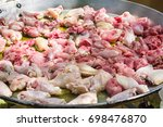 Small photo of Process of frying rabbit and chicken juicy meat slices in olive oil in large flat paella skillet. Burner with open fire. Weekend picnic setting, summer. Lifestyle.