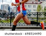 Small photo of man running city marathon in compression socks and hand multisport watch