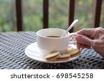 Small photo of A cub of morning coffee and cookie with an old right female hand on a dark table with green nature background.