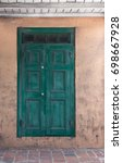 Small photo of Vertical image of a rustic wood double door painted teal / green, with clerestory windows in New Orleans, Louisiana. Under white overhang. Accommodates text. Happy to alter to fit your needs.