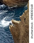 Small photo of View down along the steep, bizarrely shaped, spiky cliff with surge between rocks at the outer rim of volcanic crater island Ilheu de Vila Franca do Campo, Sao Miguel, Azores, Portugal, 2010