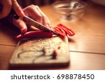 female hands cutting red chilly ... | Shutterstock . vector #698878450