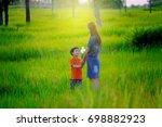 little boy giving flower to his ... | Shutterstock . vector #698882923