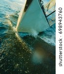 Small photo of Yachting on sail boat bow stern shot splashing sea water. Sporty transportation conept.