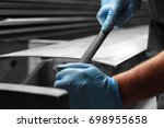 Small photo of Man filing deburring a metal panel with a file