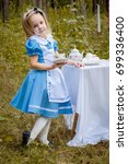 "Small photo of ""Alice in Wonderland"" styled photoshoot in forest. Girl in light blue dress drink tea."