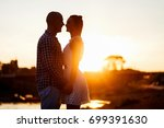 a sultry couple at sunset.... | Shutterstock . vector #699391630