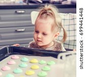 Small photo of A Little Helper. Mom teaches daughter to doing multicolored macarons