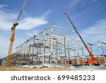 Structure building of steel structure roof truss frame installation by mobile crane under the construction building in the factory with blue sky - stock photo