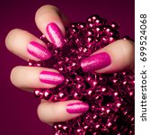 Small photo of Shiny glittering pink nails with pink pearl jewel on purple background. Manicure and nail care concept.