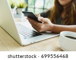 woman use smartphone on desk in ... | Shutterstock . vector #699556468