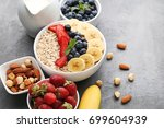 oat flakes in bowl with berries ... | Shutterstock . vector #699604939
